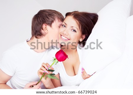 young man kissing his beautiful girlfriend and giving her a rose - stock photo