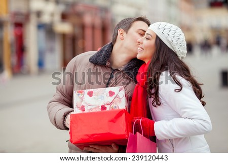 Young man kissing his girlfriend and giving her presents - stock photo
