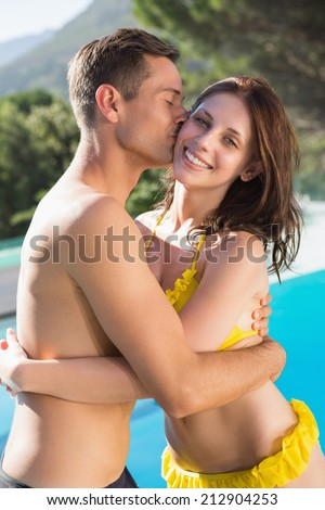 Young man kissing woman by swimming pool on a sunny day - stock photo