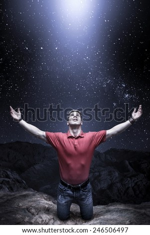 Young man knelt before a light from the sky - stock photo
