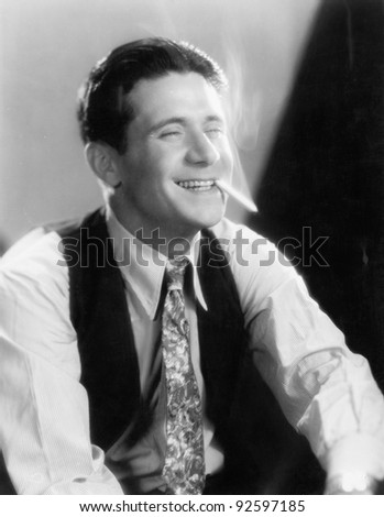 Young man laughing and smoking a cigarette - stock photo