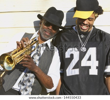 Young man laughing next to senior man with trumpet - stock photo