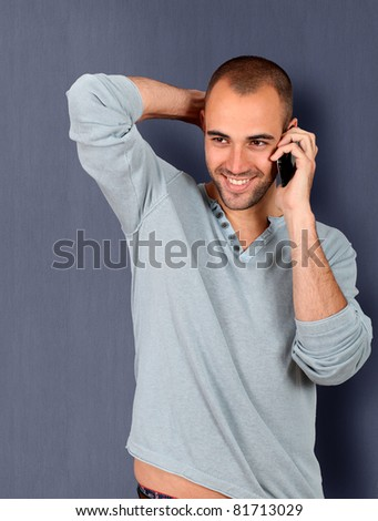 Young man leaning on blue wall with mobile phone - stock photo