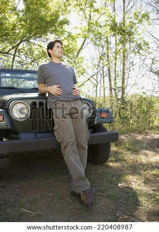 Young man leaning on jeep in woods - stock photo
