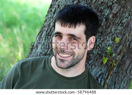 Young man leaning on tree is looking at camera. - stock photo