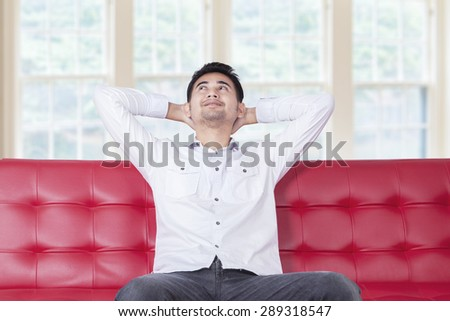 Young man leans on couch and looks happy, looking up while thinking something - stock photo