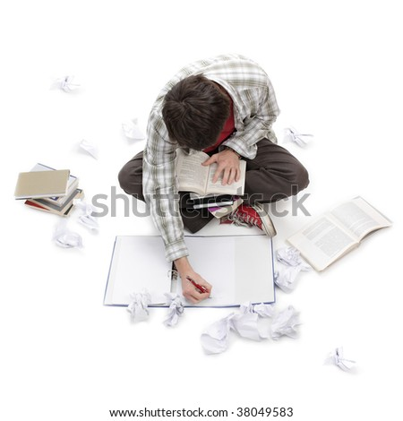Young man learning surrounded by books, exercise books and crushed paper - stock photo