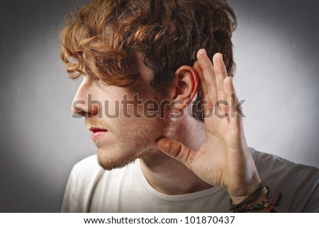 Young man lending an ear to something - stock photo