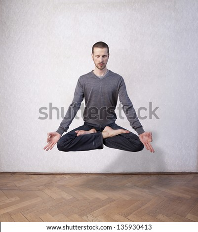 young man levitating in yoga position, meditation - stock photo