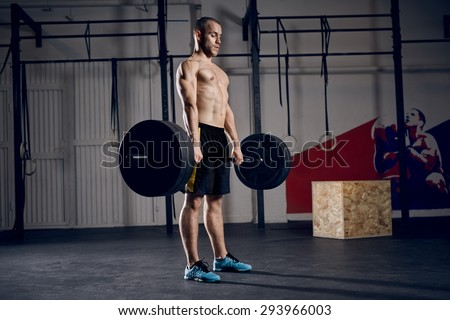Young man lifting barbells during deadlift workout - stock photo