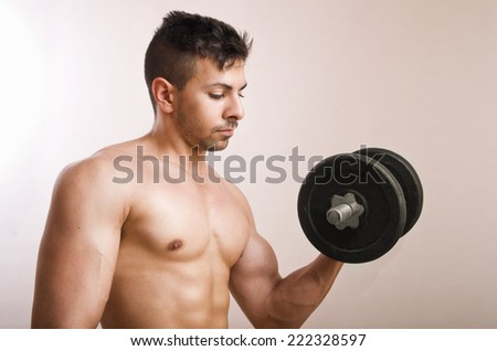 Young man lifting weights in studio shot - stock photo