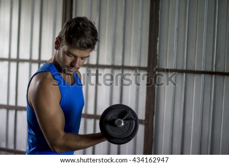 Young man lifting weights with his right arm during a workout at a gym located in a garage. He looks at his pumped biceps. - stock photo