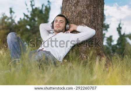 Young man listen music - enjoy - repose in grass. Guy leaning against a tree relaxing - resting. Outdoors - outside - stock photo