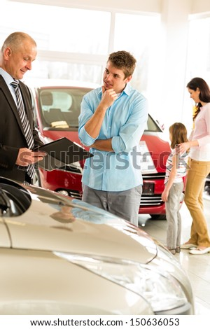 Young man listening to car agent in showroom - stock photo