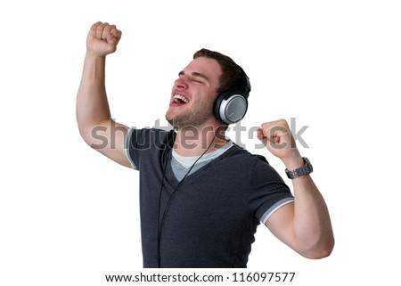 Young Man Listening to music and dancing with arms in air - stock photo