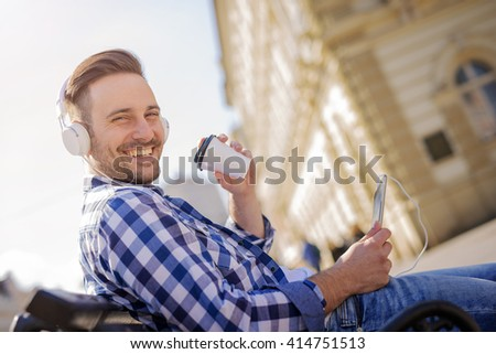 Young man listening to music on a smart phone.He is listening music on smart phone in the city. - stock photo