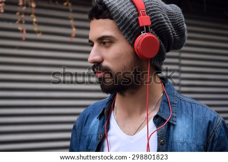 Young man listening to music with red headphones. - stock photo