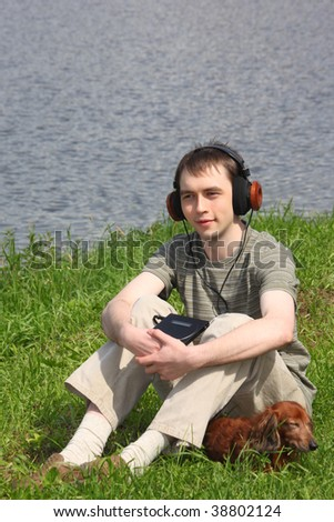 Young man listens music in headphones sits on grass with his dachshund ashore - stock photo