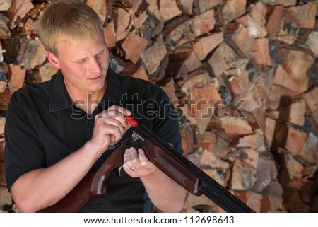 Young man loading a cartridge into a double barrel shotgun in front of a stack of firewood - stock photo