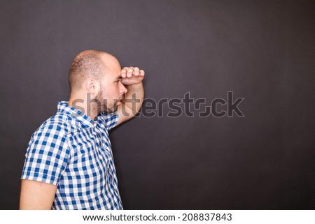 young man look far away isolated on black background - stock photo
