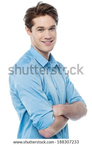 Young man looking at camera with arms crossed - stock photo