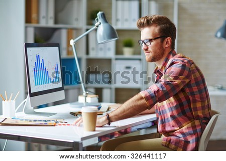 Young man looking at financial chart reflecting changes in market development - stock photo