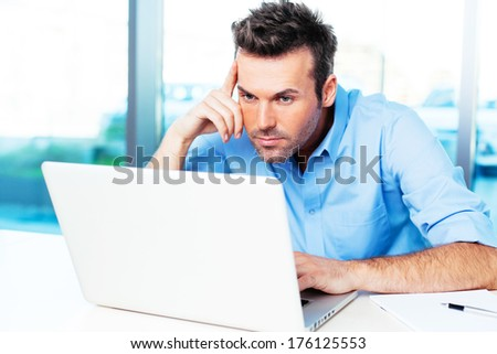 Young man looking at his laptop and surfing the web - stock photo