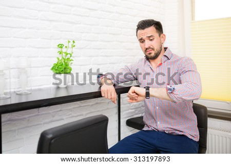 Young man looking at his watch with confused face - stock photo