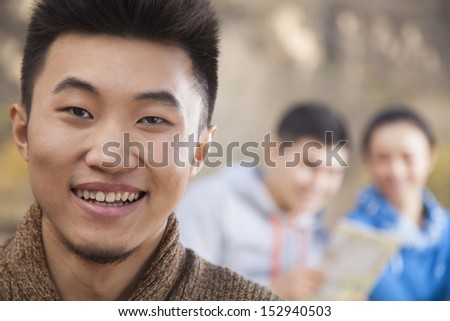 Young man looking at the camera, friends looking at the map on the background, portrait - stock photo