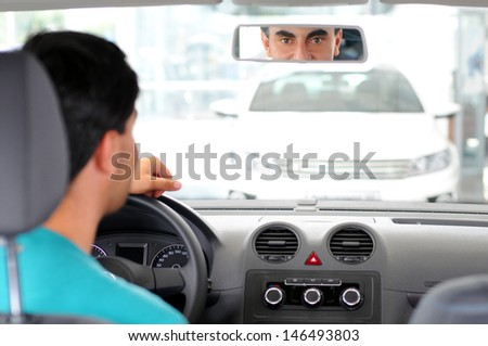 Young man looking car that wants to buy in the showroom - stock photo