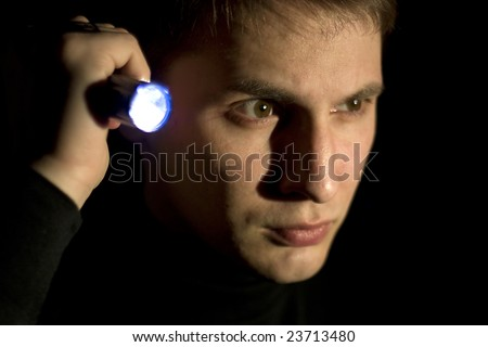 young man looking for something in the dark - stock photo