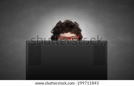Young man looking out above laptop monitor - stock photo