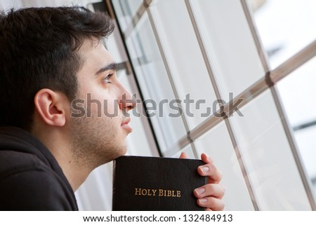 Young man looking outside with Bible in hand - stock photo