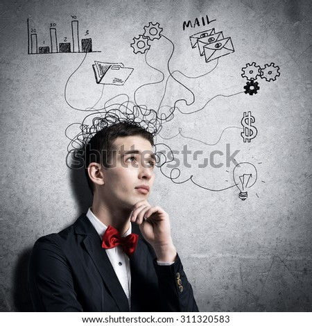 Young man looking thoughtfully at sketches on wall - stock photo