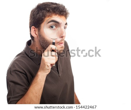 young man looking through magnifying glass - stock photo