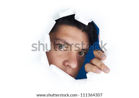Young man looking through the hole in the white paper - stock photo