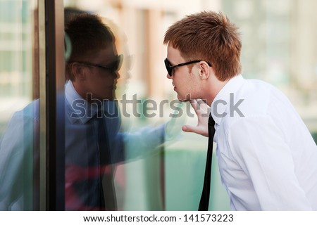 Young man looking through the window - stock photo