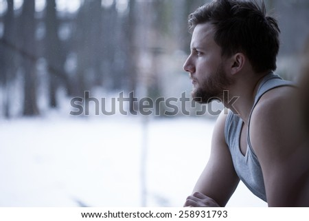 Young man looking through the window and thinking - stock photo