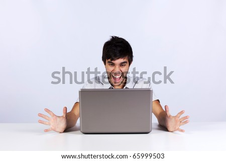 Young man looking to something terrible and screaming to his laptop - stock photo