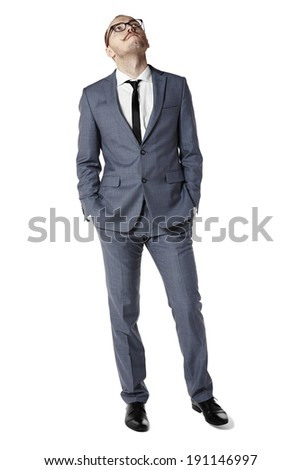 Young man looking up and wait for something. Hands in pockets - stock photo