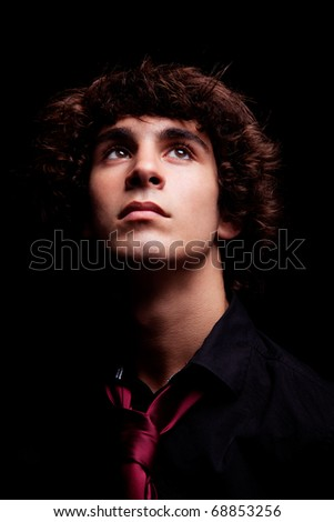 young man looking up , isolated on black, studio shot - stock photo
