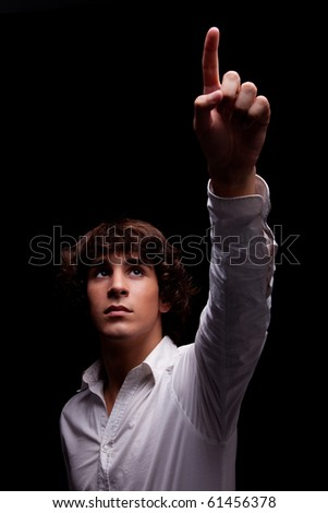 young man  looking up to the light and pointing - sign of faith , isolated on black, studio shot - stock photo