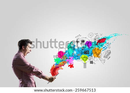 Young man looking with shock in tablet pc - stock photo