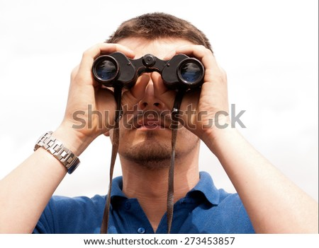 Young man lookinhg through binoculars - stock photo