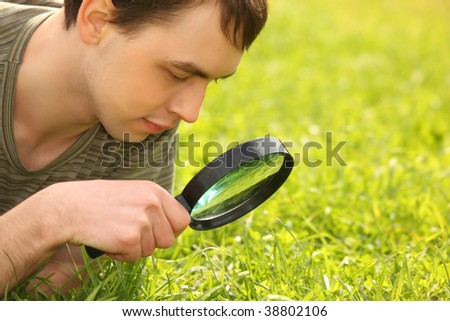 young man looks through magnifier on grass field - stock photo