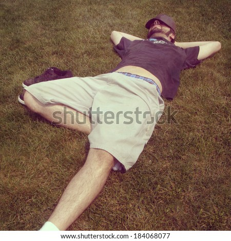Young man lounging in grass, instagram style - stock photo