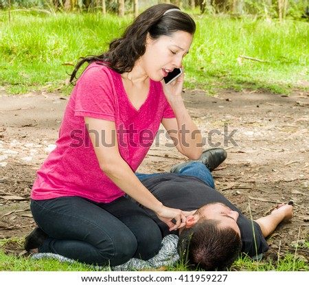 Young man lying down with medical emergency, woman sitting by his side calling for help and checking pulse, outdoors environment - stock photo