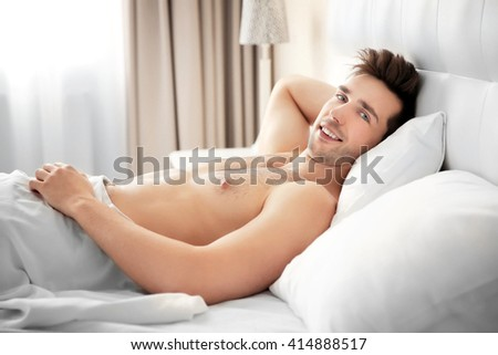 Young man lying in bed at home - stock photo