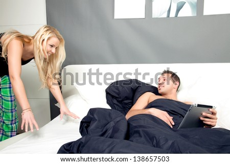 Young man lying in bed on a lazy day with his tablet computer looking over his shoulder at his playful wife who is trying to attract his attention - stock photo