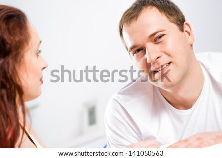 young man lying in bed with his girlfriend, spend time together at home - stock photo